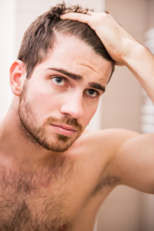 Foto de Handsome man is checking hairline while looking at the mirror. - Imagen libre de derechos