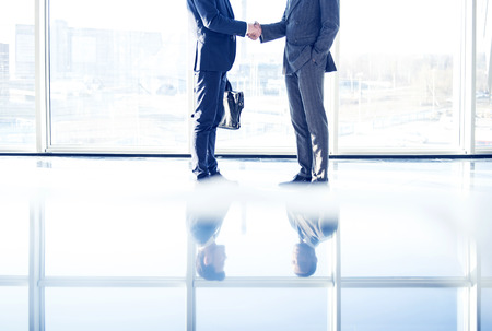 Foto de Two young businessmen are shaking hands with each other standing in a room with panoramic windows. - Imagen libre de derechos