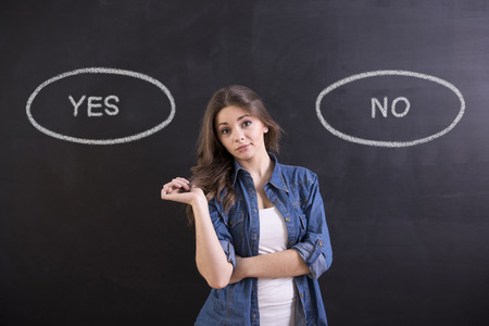 Photo pour Young woman is standing on blackboard background and thinking: yes or no. - image libre de droit