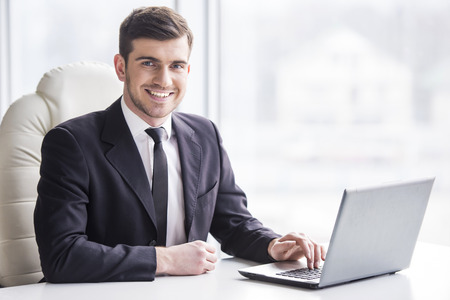 Photo pour Handsome businessman is working with laptop in office is looking at the camera. - image libre de droit