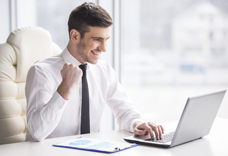 Photo for Young, happy businessman is working in his office. - Royalty Free Image
