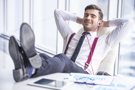 Young man in suit listening music in headphone in office.