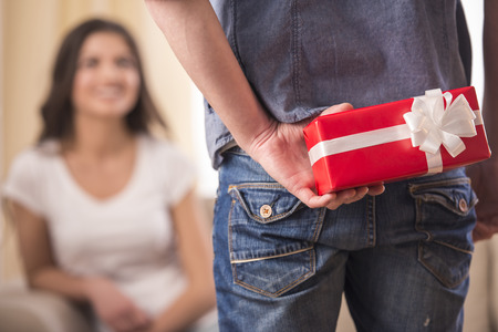 Photo for Guy is holding gift behind him is trying to surprise his is waiting girlfriend at home. Focus on boy. - Royalty Free Image