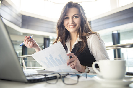 Photo pour Younge beautiful business woman working with documents in the office - image libre de droit