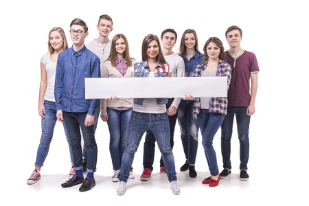 Photo for Happy young students standing and smiling. White table with empty space for the text. Isolated on white background. - Royalty Free Image