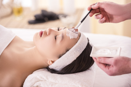 Foto de Spa therapy for young asian woman receiving facial mask at beauty salon. - Imagen libre de derechos