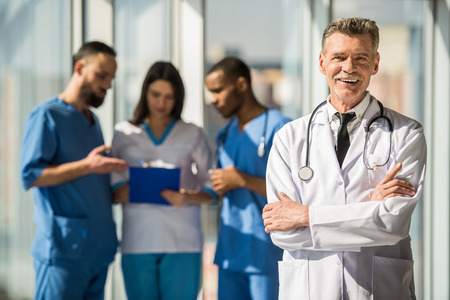 Photo pour Portrait smiling mature male doctor standing with arms crossed. The background doctors speaking. - image libre de droit