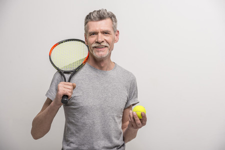 Photo pour Senior male trainer with tennis racket and tennis. - image libre de droit