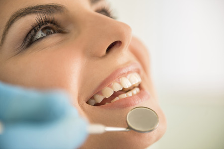 Foto de Close up of Dentist hands working attractive female teeth. - Imagen libre de derechos