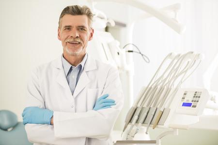 Photo pour Portrait of a smiling senior dentist in dental clinic. - image libre de droit
