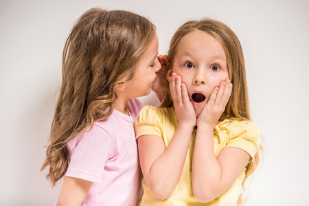 Photo for Girl telling a secret her friend on grey background. - Royalty Free Image