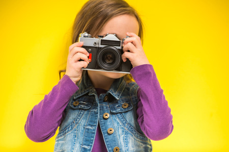 Photo for A little cute girl making photo on yellow background. - Royalty Free Image