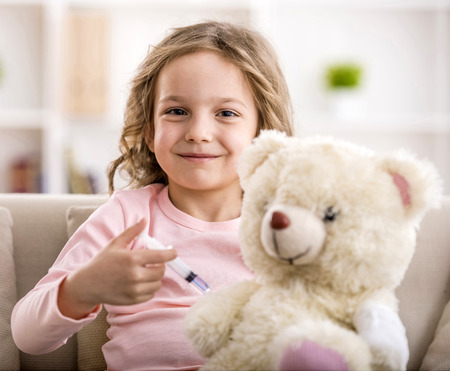 Photo for Little girl makes injection to teddy bear. Smiling and looking at the camera. - Royalty Free Image