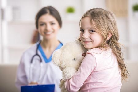 Foto de Young smiling female doctor and her little patient  with teddy bear. - Imagen libre de derechos