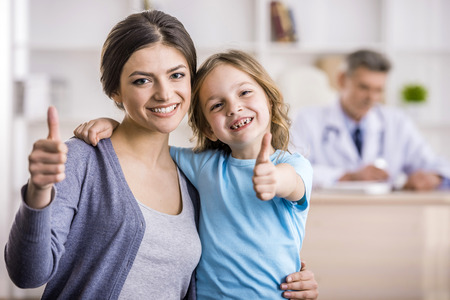 Foto de Smiling mother and her little daughter at the doctor.  - Imagen libre de derechos