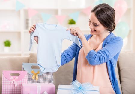 Foto de Happy pregnant woman is sitting with presents at a baby shower. - Imagen libre de derechos