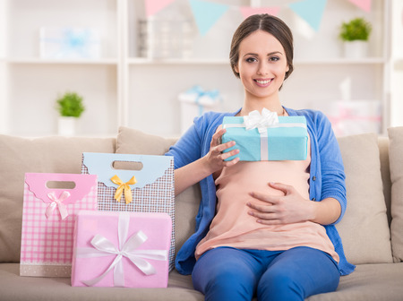 Foto de Happy pregnant woman is sitting with presents at a baby shower. - Imagen libre de derechos