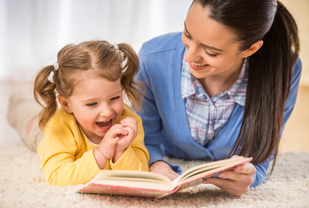 Photo pour Young mother is reading a book to her cute daughter. - image libre de droit