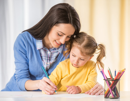 Foto de Mother and daughter are having fun while drawing at home. - Imagen libre de derechos