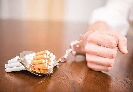 Photo pour Man hand with handcuffs and cigarettes on the table. The concept of smoking dependence. - image libre de droit
