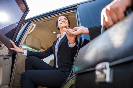Photo pour Young beautiful smiling businesswoman in suit coming out of her luxurious car. - image libre de droit