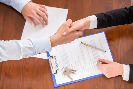 Foto de Top view of handshake of a real estate agent and a client. - Imagen libre de derechos