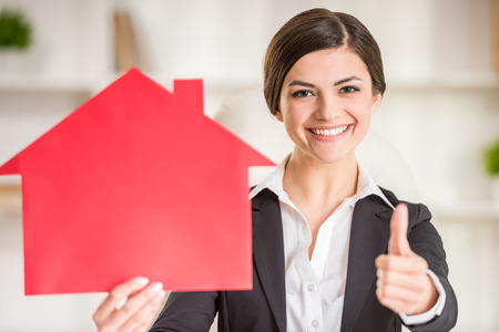 Photo pour Happy realtor woman is showing home for sale sign and thumbs up. - image libre de droit