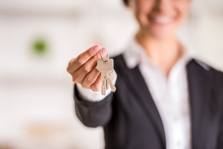 Photo for Realtor is giving the keys to an apartment to clients. Focus on the keys. - Royalty Free Image