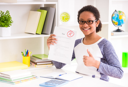 Photo pour Young mulatto schoolgirl  in glasses sitting at the table and  showing perfect test results on colorful background. - image libre de droit