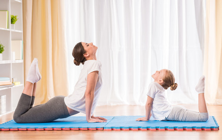Photo pour Mother and daughter doing yoga exercises on rug at home. - image libre de droit