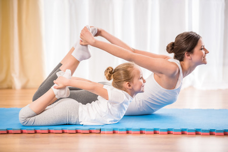 Photo for Mother and daughter doing yoga exercises on rug at home. - Royalty Free Image
