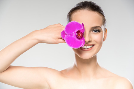 Photo pour Beautiful face of young woman with purple orchid flower. Skin care treatment. - image libre de droit