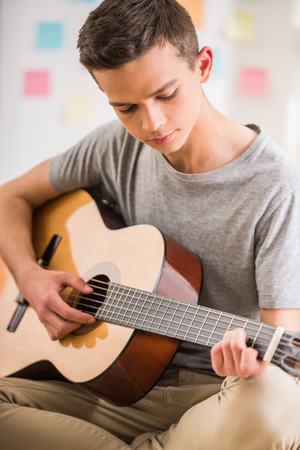 Photo pour Male teenager sitting at home and playing guitar. - image libre de droit