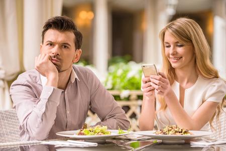 Foto de Man is getting bored in restaurant while his woman looking at phone. - Imagen libre de derechos