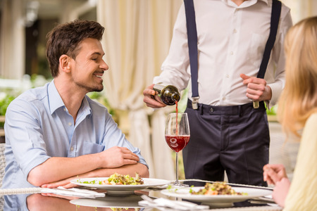 Photo for Cheerful couple in a restaurant ordering wine. Romantic dinner. - Royalty Free Image