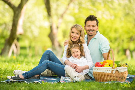 Photo for Image of happy young family having picnic outdoors. - Royalty Free Image
