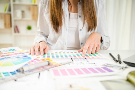 Foto de Close-up of young designer working with color samples in her office. - Imagen libre de derechos