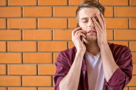 Foto de Young tired man talking on phone on brick wall background. - Imagen libre de derechos