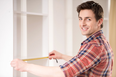 Photo pour Young man measuring home furniture with measure tape. Repair concept. - image libre de droit