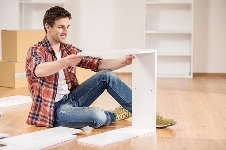 Photo pour Young man dressed casual assembling furniture in new house. - image libre de droit