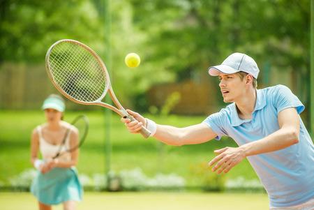 Photo pour Couple playing doubles at the tennis court. Healthy lifestyle concept. - image libre de droit