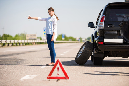 Foto de Red warning triangle with a broken down car on the road. Woman catching car. - Imagen libre de derechos
