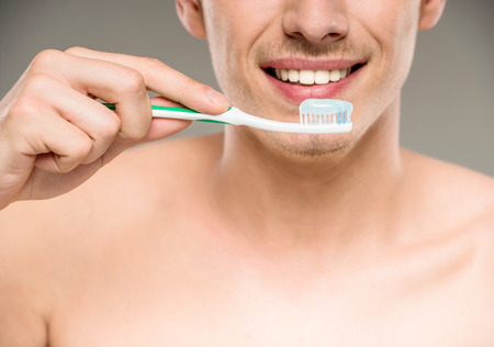 Photo pour Handsome man cleaning teeth with tooth brush in bathroom. - image libre de droit