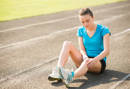Photo pour Female athlete runner touching foot in pain due to sprained ankle. - image libre de droit