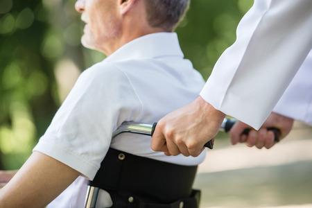 Foto de Male nurse walking with senior patient in wheelchair in garden near hospital. Closeup. - Imagen libre de derechos