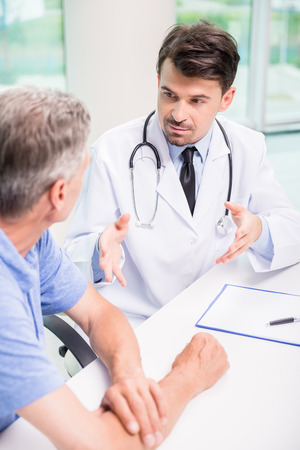 Photo pour Male doctor talking with patient seriously at clinic. - image libre de droit