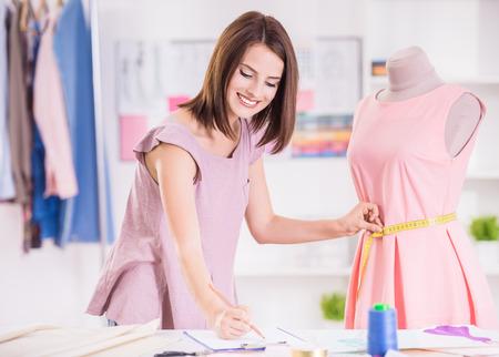 Foto de Female fashion designer taking measurement and writing it down. - Imagen libre de derechos