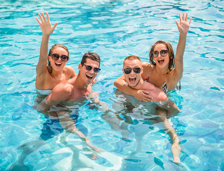 Photo for Beautiful young people having fun in swimming pool, smiling. - Royalty Free Image