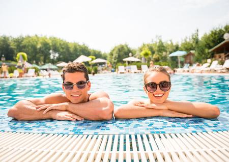 Foto de Young couple relaxing in resort swimming pool. - Imagen libre de derechos