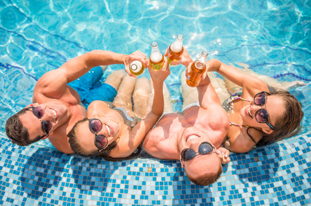 Photo for Top view of beautiful young people having fun in swimming pool, smiling and drinking beer. - Royalty Free Image